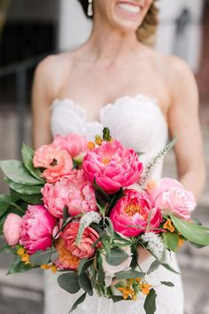 Beautiful bright pink bridal bouquet with coral charm peonies, ranunculus, and roses.