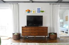 Finally....a way to decorate that empty space over the television...gotta try it.  Young House Love - One young family + one old house = love.