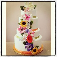 4 tier white fondant cake with green and orange color combination and vibrant gum paste flowers cascading down the cake.