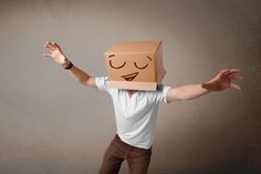 Young man gesturing with a cardboard box on his head with smiley face