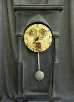 """Haunted Clock"", made by William Bezek. Made from plywood, scrap lumber, and plastic wedding cake pillars; the clock face was sculpted from Epoxy clay on a wood round. Used a battery operated clock kit with a pendulum from the hobby shop and upgraded the clock hands to something more ornate. The whole was finished in oil paints, varnished, and waxed."