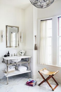 Gorgeous bathroom with antique, glamorous details, marble sink and incredible light fixture