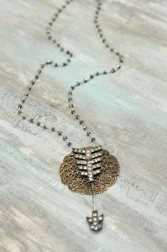 Piercing love    1930's rhinestone arrow pin layered over antique brass filigree disc on sterling and pyrite chain