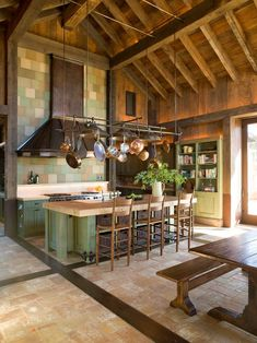 If i ever get a country home ... Gorgeous, unique kitchen. Rustic painted cabinets, beams, island with baskets, bench table, pot rack.