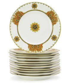 A SET OF TWELVE RUSSIAN PORCELAIN DINNER PLATES, KORNILOV BROTHERS MANUFACTORY, ST. PETERSBURG, CIRCA 1900 the borders with Pan-Slavic ornament in red, yellow and black, centered with a flowerhead, with stamped factory Made in Russia by Kornilow Brothers, with 47 in red overglaze