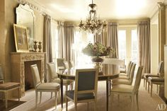 The dining room is furnished with a table and chairs from Kasler's line for Hickory Chair; the room's dark-leather-clad chairs are vintage Jansen, the silver-plate punch bowl is by Ralph Lauren Home, the custom-made wall covering is by de Gournay, and the sisal is by Stark Carpet.