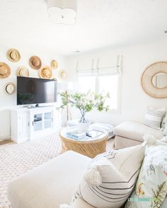 Bright and white den area with large L-shaped Pottery Barn sofa rattan. mirror greenery cane coffee table hat wall and throw pillows. Interior, Cheap Decor, Home Remodeling, Pottery Barn Sofa, Cheap Home Decor, Home Decor, House Interior, Spring Home, Fireplace Decor