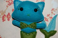 Mercat! Ha!     The Feltery makes awesome cute felt cats. https://www.thecraftstar.com/shopDetails/102/The_Feltery/    Or Etsy -     Meet Cora the Mermaid Cat  http://www.etsy.com/shop/feltery