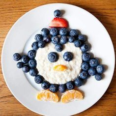Porridge penguin. Cute! With blueberries, satsuma and strawberry.