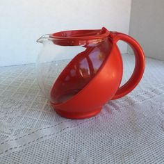Vintage red plastic and glass coffee pot or carafe.  ABOUT THIS ITEM  Pot is circular and roly poly in shape, class carafe in a red plastic holder with handle.  Unmarked coffee carafe, I havent been able to locate another one like it for identification.  Great mid century design, perfect for retro or French country kitchen decor. In great vintage condition, no chips, cracks, or damage, some staining between the plastic and glass. Pot is 4 1/2 inches tall and 2 3/4 inches in diameter...