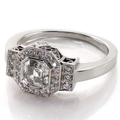 Design 2163 from Knox Jewelers is a modified version of our Art Deco design. This ring features a bezel set .90ct Asscher center diamond surround by a halo with two side bars of diamonds. The side view of the ring reveals filigree and a smaller, surprise diamond on each side. This surprise diamonds are also Asscher cut.  #halo #artdeco #asscher