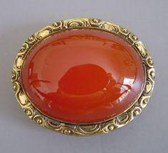 "oval carnelian cabochon brooch in gold tone setting, 1-3/4""."