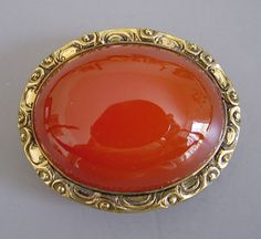 "oval carnelian cabochon brooch in gold tone setting, 1-3/4""."