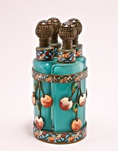 1920s French perfume tantalus, four bottles (one lip flake), cased blue-green crystal, filigree metal stopper heads, champleve enameled metalwork