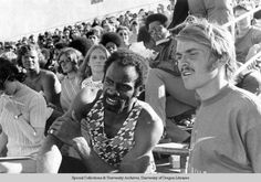 Black and white photo of University of Oregon distance runner Steve Prefontaine (right) with Texas Southern sprinter Robert Taylor, watching action on the track at the 1972 Olympic Trials held at Hayward Field. Prefontaine finished 4th in the 5000 meters at the Munich Olympic Games and Taylor won gold in the 4 x 100 relay and silver in the 100 meters. ©University of Oregon Libraries - Special Collections and University Archives