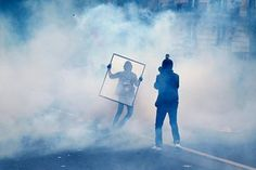 A protester is protected behind an acrylic sheet during clashes with riot police during the demonstration against proposed labour reforms in Paris