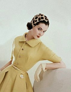 """Model is wearing a Chrysanthemum yellow pleated shirt dress in Uxbridge Shetland wool and a leopard print cap, August 1955."""