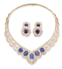 A SET OF SAPPHIRE AND DIAMOND JEWELLERY, BY VAN CLEEF & ARPELS   Comprising a necklace, the front set with five oval-cut sapphires, weighing 6.38, 9.00, 10.10, 8.95 and 8.62 carats, each within a circular-cut diamond surround to the diamond-set swag and line neckchain; and a pair of ear clips, each designed as overlapping pavé-set diamond flowers with cushion-shaped sapphire centres, mounted in 18k gold.  Signed Van Cleef & Arpels,