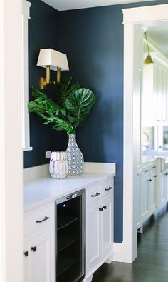 Blue and white pantry features a glass front mini wine fridge fixed between white shaker cabinets accented with oil rubbed bronze knobs and pulls and a white quartz countertop lined with a white quartz backsplash and contrasted with a dark blue wall paint lit by an antique brass sconce.