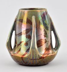 "A Clement Massier Golfe-Juan Lustre Vase       The tapering four-handled vase with green-copper lustre image of branches with leaves and berries, . 5-3/4""H x 6""W, marked in the glaze and impressed mark on the underside."