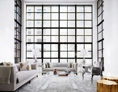 NYC apartment features super high ceilings, floor to ceiling windows and an architectural glass railing staircase