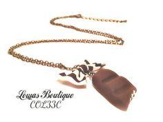 Collier Barre de Chocolat Ce collier est constitué d'une barre de chocolat en fimo avec un petit noeud en tissu, le tout monté sur une chaine en bronze.   Chaine d'extension inclus. Fermoir mousqueton inclus. Dimension: 63 cm