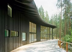 Black-painted slats in different widths and thicknesses create uneven ridges on the walls of this lakeside house in a Finnish pine forest.