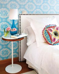 tourquoise patterned wallpaper+ethnic cushion versus white bedroom