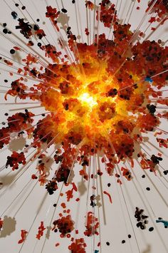 A delusory image. An explosion composed by a lightbulb and tons of red, orange and yellow gummy bears and worms.