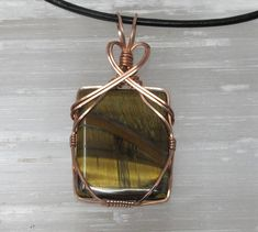 Handmade, one of a kind, copper wire wrapped tigers eye pendant. Arrives in a gift box including 18 leather cord necklace and polishing pad to keep it shining like new.