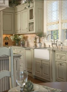 love the pale celadon green color on the kitchen cabinets.  The beadboard and iron pulls keep the vintage feel