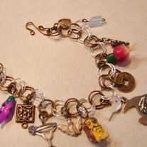 """Several little items adorn this charm bracelet.  Looks to be an apple, Owl, gemstone, champaign glass and more items along with a tiny bronze heart.  Colors of wire included antique bronze and silver.  Its slightly over 7 1/2"""".  Free shipping in the USA    www.carolesjewelry.com"""