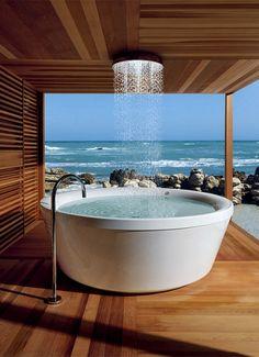 Der Inbegriff von Entspannung: Eine freistehende Rundbadewanne mit Regendusche verwandelt Ihr Badezimmer in eine Wellnessoase! Die verschiedenen Holztöne und die großen Fenster vollenden das Wellness-Badezimmer.
