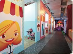 The concept for this play area in Singapore was created by Smadar Ron at The City by Littlez. Wide-format printed images were used to create everyday settings, such as shops, for children to play in.
