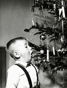 Kerstmis, kerstversiering. Jongen blaast het vlammetje van echte kerstboomkaarsjes uit.
