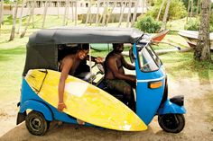 Surfers with a yellow surfboard in a colourful blue rickshaw on the beach in Sri Lanka. Photo by: David Crookes