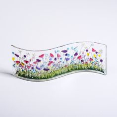 Wild gardens are vibrant with colours and butterflies during the summer months. This piece will make you smile even on the dullest of days. Before I fire the piece I hand paint some of the detail then the piece is made by fusing different coloured glass together at a very high temperature in a kiln. The piece is then bent into a wave shape using a mould. It is approximately (L) 25cm x (H) 7.5cm x (D) 2cm These curves look great on a window sill allowing the light to really shine through, or…
