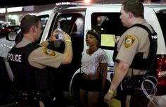 Police take a mug shot of a protester who was detained in Ferguson, Missouri, August 10, 2015. Protesters regrouped in Ferguson, Missouri, on Monday evening after a state of emergency was declared, aimed at preventing a repeat of violence the night before on the anniversary of the police shooting of unarmed black man Michael Brown. REUTERS/Rick Wilking