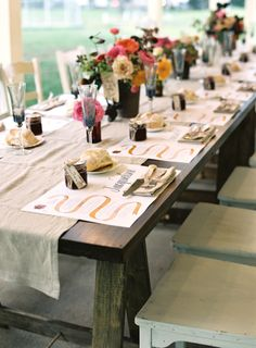 rustic, vintage, chic is achieved with this table setting. personalized plate mats are a nice touch and the consistency of the florals along the family style seating adds interest and colour.
