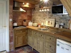 Adorable, tiny cottage kitchen, with exposed stone wall.
