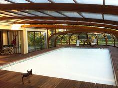 Cubierta de piscina en madera, alta, curva y con murales. Al estilo porche. La cubierta con murales va directamente empalmada a la casa, en posición paralela.Esta configuración es ideal para las piscinas situadas muy cerca de un edificio.