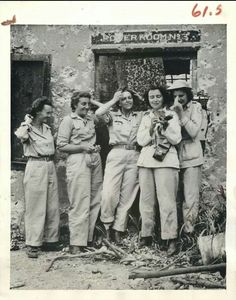 """1945- U.S. WACs and Red Cross girls pull out their face powder below sign reading """"Powder Room No. 3"""" during tour of bomb-blasted Corregidor."""