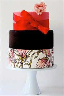 Layers of hand-painted flowers, rich chocolate and a red ribbon are topped with a hand-made sugar flower.