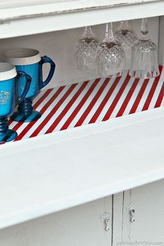 DIY beverage cabinet from used furniture. Red and white shelf paper make it shine.