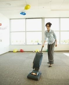 Businesswoman vacuuming after office party