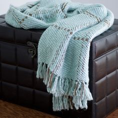 Perfect tossed across your favorite reading chair or draped over the sofa, this eye-catching throw showcases a plaid motif and tassel fringe.