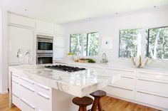 Modern all white L-shaped kitchen design with chunky marble island countertop.