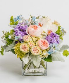 Morning Dew A stunning collection of pastel summer tones including garden roses, orchids, hydrangea and delphinium is designed in our signature glass cube vase.