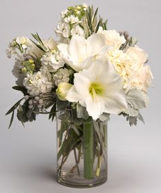 Snowflake A lovely collection of pristine white blooms including amaryllis, roses and hydrangea is designed in our signature glass cylinder vase.