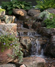 A Pondless Waterfall allows you to experience the soothing sights and sounds of moving water with less maintenance and expense than The Ecosystem Pond. A Pondless Waterfall is often the perfect water feature for front yards, smaller spaces, public areas Garden Waterfall, Waterfall Fountain, Pond Landscaping, Backyard Water Feature, Water Features In The Garden, Garden Fountains, Garden Pool, Dream Garden, Outdoor Gardens